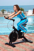 Smiling girl on bicycle training apparatus outdoor — Stock Photo