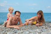 Parents with child on sea coast build pyramid of stones — Stock Photo