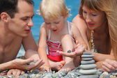 Closeup parents with child on sea coast and pyramid of stones — 图库照片