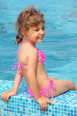 Little girl sits on border of pool — Stock fotografie