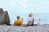 Parents with child sit on seacoast, rear view — Stock Photo