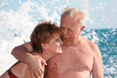 Portrait of aged pair in sea surf — Stock Photo