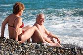 Aged pair sit on pebble beach — Stock Photo
