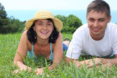 Young couple lies on grass — Stock Photo