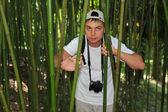 Photographer in bamboo grove in Sochi arboretum — Stock Photo
