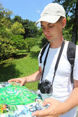 Photographer looks on map in sochi arboretum — Stock Photo