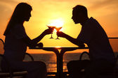 Man and woman clink glasses on sunset outside — Stock Photo
