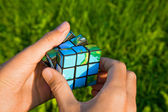Cube in the manner of planets land on palm on background — Stock Photo