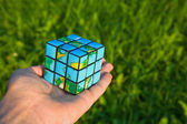 Cube in the manner of planets land on palm on background of the — Stock Photo
