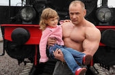 Strong shirtless man on railroad with little girl on hands — Stock Photo
