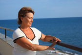 Portrait of middleaged woman on balcony over sea — Stock Photo