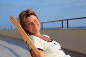 Middleaged woman in lounge on veranda over sea — Stock Photo