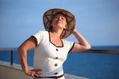 Portrait of middleaged woman in hat on balcony over sea — Stock Photo