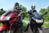 Two motorcyclists standing on country road — Stock Photo
