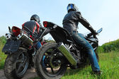 Two motorcyclists standing on country road, back view — Stock Photo