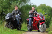 Two motorcyclists standing on country road, without helmets — Stock Photo