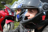 Portrait of two motorcyclists sitting on country road near bike — Stock Photo