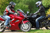 Two motorcyclists standing on country road, side view — Stock Photo