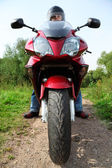 Motorcyclist standing on country road, closeup, front view — Stock Photo