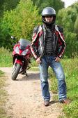 стоя на проселочной дороге возле велосипед мотоциклист — Стоковое фото