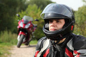 Motorcyclist and his bike on country road — Stock Photo