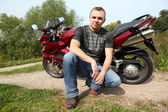 Motorcyclist sitting on country road near bike — Stock Photo