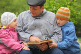 Grandfather reads book for kid — Stockfoto