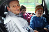 Man and kids sit in the car — Stock Photo