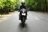 Motorcyclist goes on road, front view — Stock Photo
