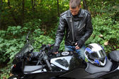 Motorcyclist and his bike in forest — Stock Photo