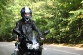 Motorcyclist goes on road — Stock Photo