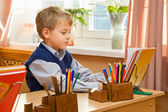 Young schoolboy sitting Behind a school desk — Stock Photo