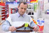 Homme âgé dans la boutique avec cintres pour vêtements en mains — Photo