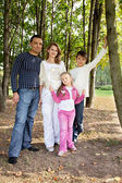 Smiling happy family of four in park — Stock Photo