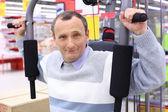 äldre man i butik på sport motionscykel — Stockfoto