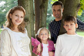 Familia feliz sonriente de cuatro al aire libre — Foto de Stock