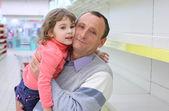Starší muž v prázdné regály v obchodě s dítětem na ruce — Stock fotografie