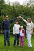 Eltern spielen mit Kindern im park — Stockfoto