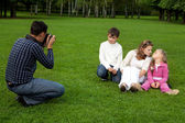 Man photographes his family outdoors — 图库照片
