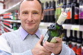 šťastný starší muž v obchodě s láhví vína v rukou — Stock fotografie