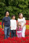 Family of four looking aside in flowering park — Stock Photo