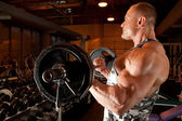 Bodybuilder in training room — Stock Photo