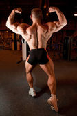 Bodybuilder back demonstrates his muscles — Stock Photo