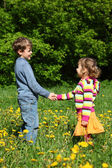 Boy and girl handshaking among blossoming dandelions — Stock Photo