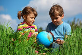 Girl and boy with globe on meadow — Stock Photo
