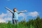 Boy standing with spreading hands on the field — Stock Photo
