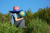 Boy in big american flag hat sits on grass and holds globe — Stok fotoğraf