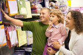 Family with little girl buy bedding in supermarket — Stock Photo