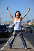 Girl stands on middle of road with rised hands — Stock Photo