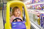 Little girl goes for drive on shoppingcarts in supermarket — Stock Photo